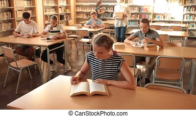 Schoolchildren preparing for lesson in school library, reading textbooks . High quality FullHD footage