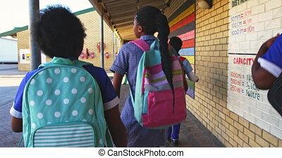 Schoolchildren running in the playground at a township ...