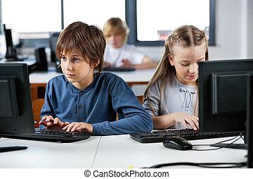 Cute little schoolchildren using desktop PC at desk in computer lab