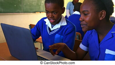 Front view close up of a young African schoolboy and schoolgirl sitting at a desk using a laptop computer together during a lesson in a township elementary school classroom, in the background classmates are sitting at their desks working 4k