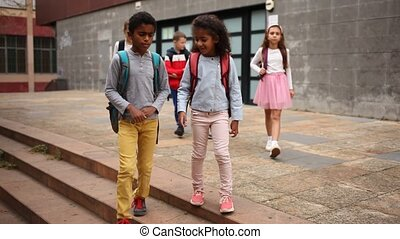 Schoolchildren walking together on the street from school. High quality FullHD footage