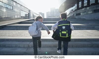 Schoolchildren with backpacks run upstairs to school for lessons. Back view.