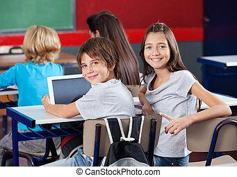Schoolchildren With Digital Tablet Sitting In Classroom