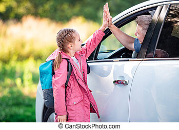 Schooler giving five to father in car