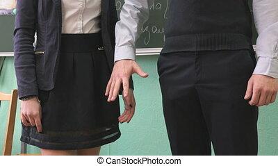 Schoolgirl and schoolboy take each other hands - School...
