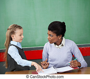Schoolgirl And Teacher Looking At Each Other At Desk