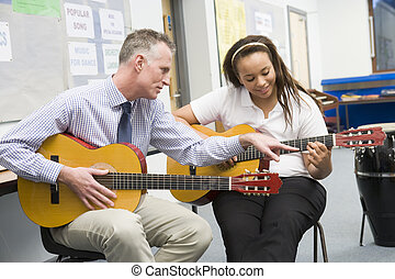 Schoolgirl and teacher playing guitar in music class