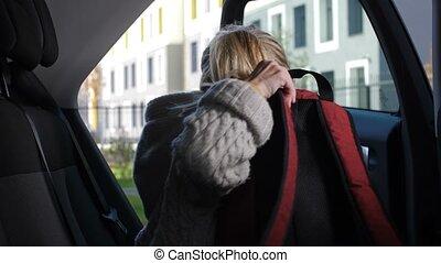 Schoolgirl arriving to school in parent's car