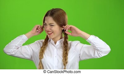 Schoolgirl closes his ears from the noise. Green screen -...