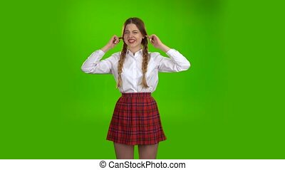Schoolgirl closes his ears from the noise . Green screen -...
