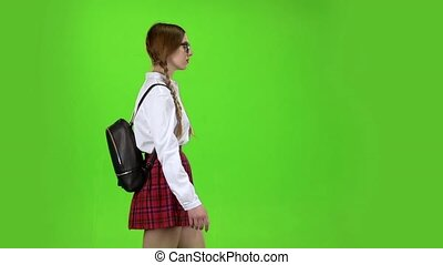 Schoolgirl comes with a backpack on her back. Green screen. Slow motion . Side view