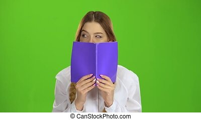 Schoolgirl covered her face with a notebook. Green screen