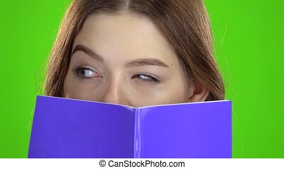 Schoolgirl covered her face with a violet notebook . Green screen. Close up