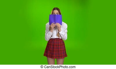 Schoolgirl covered her face with a violet notebook. Green screen