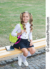 Schoolgirl cute child with backpack relax outdoors, formal education concept.