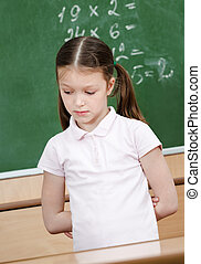Schoolgirl doesn't know the answer and puts her hands behind...