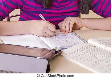 Schoolgirl doing her homework using digital tablet computer