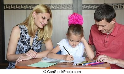 Schoolgirl doing homework with parents