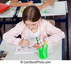 Schoolgirl Drawing At Desk In Classroom