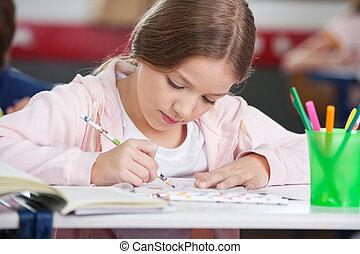 Schoolgirl Drawing At Desk