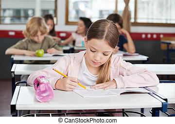 Schoolgirl Drawing In Book At Classroom