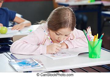 Schoolgirl Drawing In Book At Desk