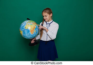 Schoolgirl girl studies globe at school on geography