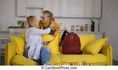 Schoolgirl giving mom goodbye kiss before school