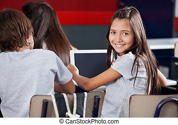 Schoolgirl Holding Digital Tablet At Desk In Classroom