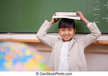 Schoolgirl holding her book on her head