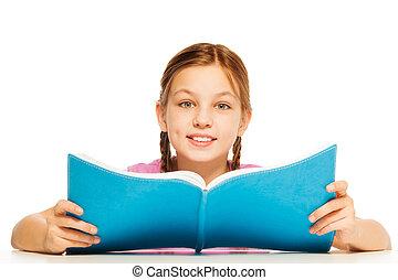 Schoolgirl holding textbook in her hands