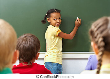 Schoolgirl - Image of schoolgirl by the blackboard looking...