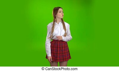 Schoolgirl in a white blouse thinks . Green screen