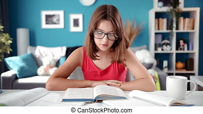 Schoolgirl in eyeglasses sitting at table and reading book...