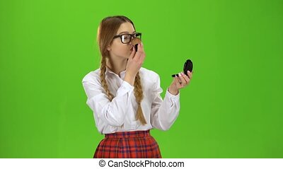 Schoolgirl in glasses powdered her nose with a brush. Green...