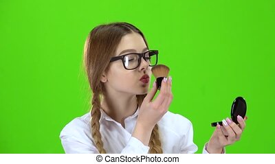 Schoolgirl in glasses powdering her nose with a brush looks in the mirror . Green screen