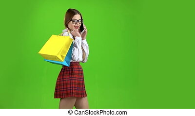 Schoolgirl in glasses speaks on the phone and holds shopping bags. Green screen. Slow motion. Side view