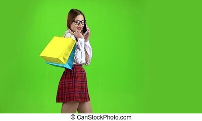 Schoolgirl in glasses speaks on the phone and holds shopping...