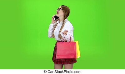 Schoolgirl in glasses speaks on the phone and holds shopping bags. Green screen. Slow motion