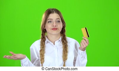 Schoolgirl in white blouse with a credit card is sad. Green screen
