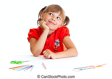 Schoolgirl is sitting at table with pencils, paints and scissors isolated