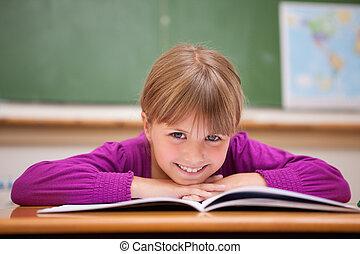 Schoolgirl leaning on a desk