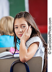 Schoolgirl Leaning On Chair In Classroom