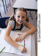 Schoolgirl looking at camera at desk in classroom