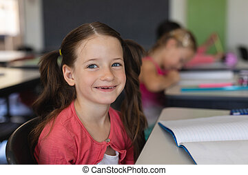 Schoolgirl looking at camera while sitting in classroom