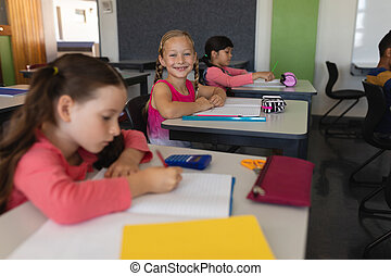 Schoolgirl looking at camera while studying in classroom
