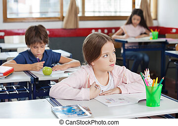 Schoolgirl Looking Away While Drawing In Classroom