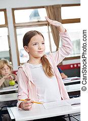Schoolgirl Looking Away While Raising Hand In Classroom