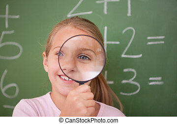 Schoolgirl looking through a magnifying glass