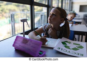 Schoolgirl looking up at desk in classroom